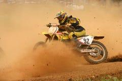 Jinete del motocrós en curva con polvo en la cara Fotos de archivo