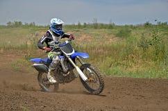 Jinete del MX en una motocicleta en una curva Foto de archivo