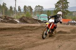 Jinete del MX en una motocicleta en una curva Imagen de archivo