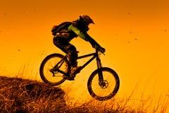 Jinete en declive de la bici de montaña en la puesta del sol Fotos de archivo