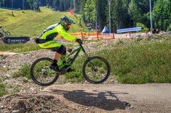 Jinete en declive de la bici que salta durante la raza de la bici de montaña Fotografía de archivo