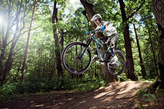 Jinete en la acción en el deporte de la bici de montaña Salte en una bici de montaña Fotos de archivo