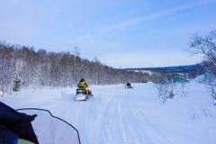 Jinete en la moto de nieve en la estación de esquí de las montañas en Amut Rusia foto de archivo