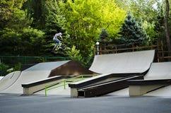 Jinete extremo de BMX en salto del casco en skatepark en la competencia Concepto de la bicicleta del deporte para la cartelera Imagen de archivo