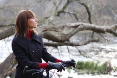 Jinete femenino joven de la bicicleta en parque del otoño Imágenes de archivo libres de regalías