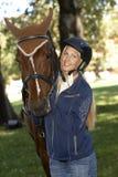 Jinete femenino que abraza la sonrisa del caballo feliz Foto de archivo