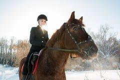 Jinete hermoso joven de la muchacha que monta un caballo en bosque del invierno Foto de archivo