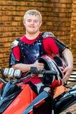 Jinete joven perjudicado de la bici del patio que sostiene el casco Foto de archivo