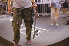 Jinete joven que sostiene un monopatín en el torneo de la competencia imagen de archivo