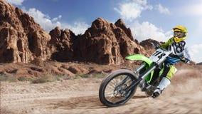 Jinete profesional de la bici de la suciedad que compite con en el desierto Fotos de archivo