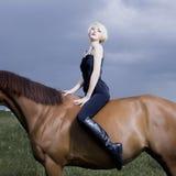 Jinete rubio hermoso de la muchacha a caballo Fotografía de archivo