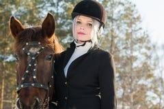 Jinete y caballo hermosos jovenes de la muchacha en bosque del invierno Foto de archivo libre de regalías