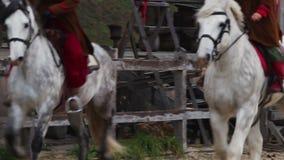 Jinetes antiguos en los caballos criados en línea pura que organizan la competencia en la calle principal metrajes
