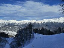 Jinetes del esquí y de la snowboard en las montañas Fotografía de archivo