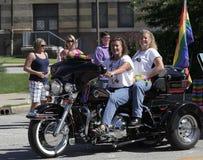 Jinetes femeninos de la motocicleta con la bandera del arco iris en Indy Pride Parade Foto de archivo libre de regalías