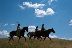 Jinetes nómadas que montan en puesta del sol Fotografía de archivo libre de regalías