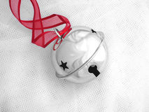 Jingle Bell. Shiny jingle bell with pretty red ribbon on a bed of white tule Royalty Free Stock Photos