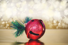 Jingle bell magic. An isolated jingle bell ornament on gold background with defocused twinkle lights in background Stock Photos