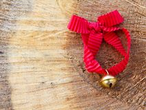 Jingle bell with red ribbon in the wood Royalty Free Stock Image