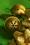 Jingle bells. Gold jingle bells on green with golden ribbons stock photo