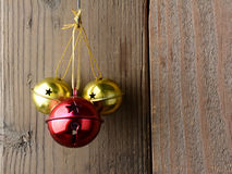 Jingle Bells. Red and Gold Jingle Bells hanging on a rustic wooden wall Stock Photo