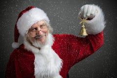Jingle Bells Santa Claus-de klok van het holdingsmetaal in zijn hand stock foto