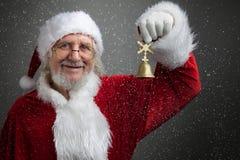 Jingle Bells Santa Claus-de klok van het holdingsmetaal in zijn hand royalty-vrije stock afbeelding