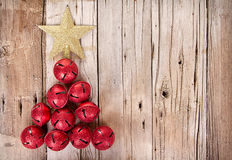Jingle bells shaped like a Christmas tree. Christmas jingle bells and golden star shaped like a Christmas tree on a rustic wooden plank Royalty Free Stock Photos