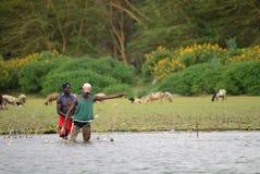 JINJA, UGANDA - OKOŁO OCT, 2017: Życie codzienne w Jinja Młodzi ludzie robią ich życie codzienne pracom przy brzeg rzeki Nil, Jin obraz royalty free