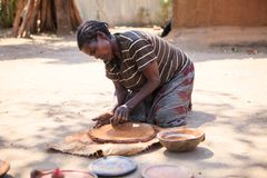 Ari tribe ceramist woman. Jinka, Omo River Valley, Ethiopia - January, 2018. Ari tribe ceramist woman preparing clay to create a traditional Ethiopian jar stock image