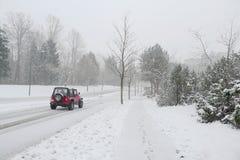 Jipe vermelho na estrada nevado do inverno Imagens de Stock