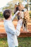 Jirafas de alimentación del muchacho joven en África Imagenes de archivo