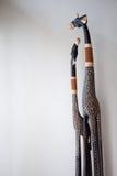 Jirafas de la talla del árbol delante de una pared blanca imagen de archivo