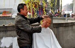 Jiu Chi miasteczko, CH: Fryzjer męski Daje ostrzyżeniu Zdjęcia Stock