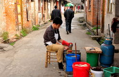 Jiu Chi Town, China: Man Peeling Potatoes Royalty Free Stock Images