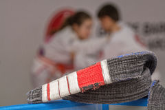 Jiu-jitsu belt. In front with athletes blurred on back Stock Photography