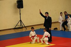 Jiu Jitsu fighters with Referee at Romanian Championship, Juniors, May 2018. Jiu Jitsu students in Kimono with Referee on tatami. Jiu-Jitsu Romanian Championship Royalty Free Stock Photography