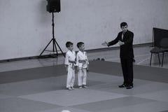 Jiu Jitsu fighters with Referee at Romanian Championship, Juniors, May 2018. Jiu Jitsu students in Kimono with Referee on tatami. Jiu-Jitsu Romanian Championship Royalty Free Stock Images