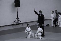 Jiu Jitsu fighters with Referee at Romanian Championship, Juniors, May 2018. Jiu Jitsu students in Kimono with Referee on tatami. Jiu-Jitsu Romanian Championship Stock Image