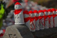 Jizo med röd hattuppställning Arkivfoto