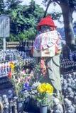Jizo munkstaty med haklappen och hatten - Japan royaltyfri fotografi