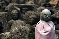 Jizo in the rocks. A small statue of the Buddhist saint Jizo, amongst roughly carved & weathered rocks stock image