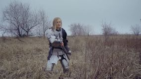 Joan of Arc in the armor stands in the field and looks out for enemies. Young blonde woman in medieval armor holds on to sword and looks around in field stock footage