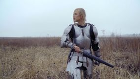 A brave blonde in armor goes to the field and clings to the sword. Joan of Arc blonde in a knight`s armor stock video