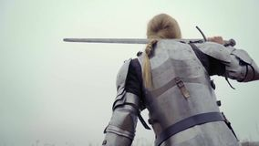 Joan of Arc in knightly armor with a huge sword on her shoulder. Blonde in medieval armor in the field stock footage