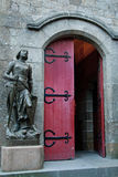 Joan of Arc Statue at Mont St. Michel. A statue of Joan of Arc stands outside a red door at the Church of St. Pierre, Mont St. Michel, France Royalty Free Stock Photo