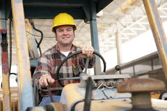 On The Job. A handsome construction worker driving a bulldozer on a construction site Stock Photos