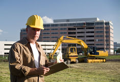 On the Job. A man in a hardhat holding a clipboard with heavy industrial eqipment in the background Royalty Free Stock Photo