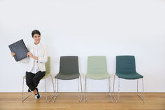 Job applicant waiting for interview with employer. Woman sitting on chair waiting for job interview Stock Photos