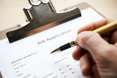 Job application. Person filling out a job application Stock Image